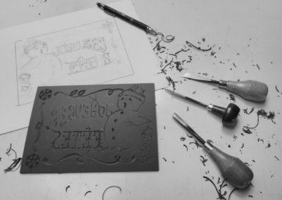 L'estampe des bonshommes de neige, linogravure en travail. Le dessin de base, la plaque de lino et les outils.