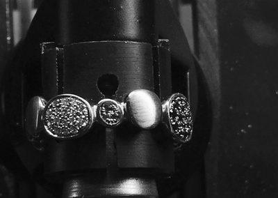 bague en forme de petits galets sertie de diamants blancs, noirs et d'émeraudes.