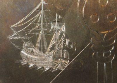 """détail de la plaque de l'estampe de """"la carte au trésor"""". Petit bateau de 2 cm de long."""
