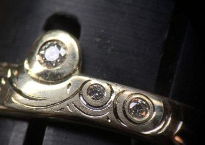 Bague en or sertie de diamants avec des traits gravés autour représentant de l'eau.
