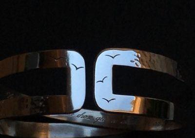 bracelet gravé de petits oiseau à l'extérieure d'une longue phrase à l'intérieur.